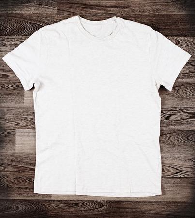 木材の背景に白の t シャツ