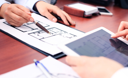 executive apartment: Real-estate agent showing house plans on electronic tablet Stock Photo