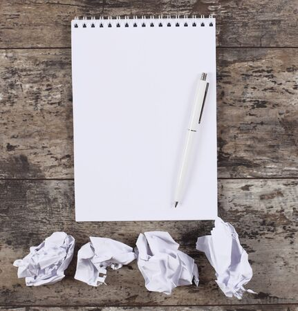 wads: crumpled wads, notebook on the wooden desk