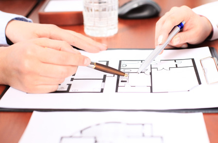 Real-estate agent showing house plans on electronic tablet Stock Photo