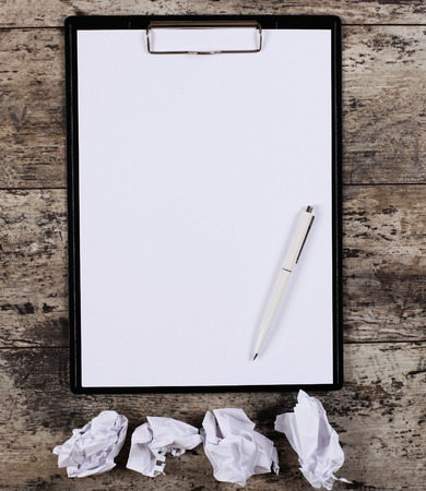 wads: crumpled wads, blank white paper sheet in a clip folder Stock Photo