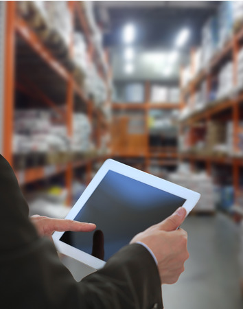 Businessman checking inventory in market on tablet computer Standard-Bild