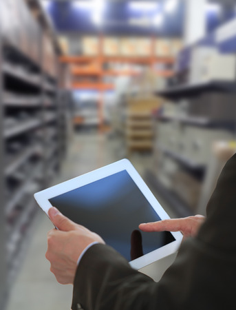 Businessman checking inventory in market on tablet computer Stock Photo
