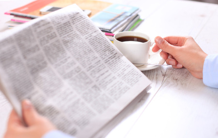 daily newspaper: Close-up of female hand on cup of coffee during reading of newspaper