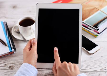 カフェの背景の上の女性の手で隔離された画面のデジタル タブレット コンピューター