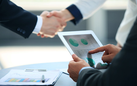 contracts: Business associates shaking hands in office Stock Photo