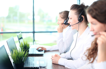 Smiling female customer service representative talking on headset with colleagues in background at office Stock fotó - 40549750