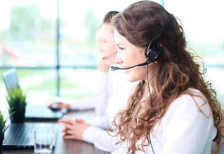 Glimlachende vrouwelijke medewerker van de klantenservice te praten over headset met collega's in de achtergrond op het kantoor van