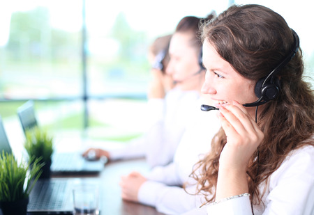 Portrait of smiling female customer service agent wearing headset with colleagues working in background at office Stock Photo - 40833294