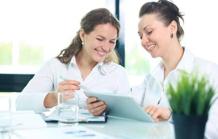 redes de mercadeo: mujeres de negocios con ordenadores PC de la tableta con la discusión en la oficina Foto de archivo
