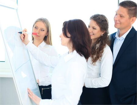 new strategy: Young business team planning a new strategy standing grouped in front of a flip chart analyzing a chart