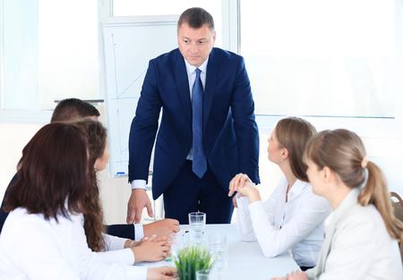 addressing: Male Boss Addressing Meeting Around Boardroom Table