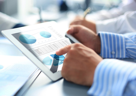 statistic: Business person analyzing financial statistics displayed on the tablet screen