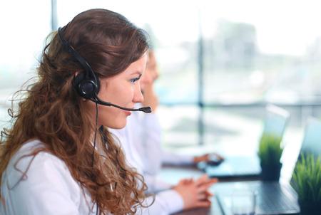 オフィスでバック グラウンドで作業している同僚とヘッドセットを着て女性顧客サービス エージェントを笑顔の肖像画
