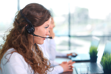 customer service representative: Portrait of smiling female customer service agent wearing headset with colleagues working in background at office