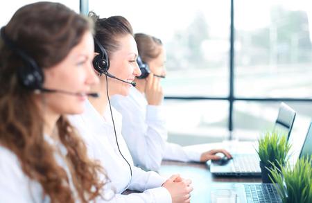 servicio al cliente: Retrato de la sonrisa agente de servicio al cliente usando auriculares con colegas que trabajan en segundo plano en la oficina Foto de archivo