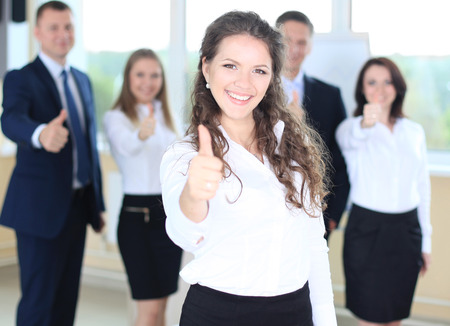 thumb up: business concept - attractive businesswoman with team in office showing thumbs up Stock Photo