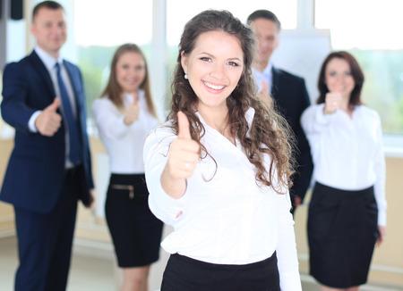 štěstí: obchodní koncept - atraktivní podnikatelka s týmem v kanceláři ukazuje palec nahoru