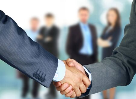 associates: Business associates shaking hands in office Stock Photo