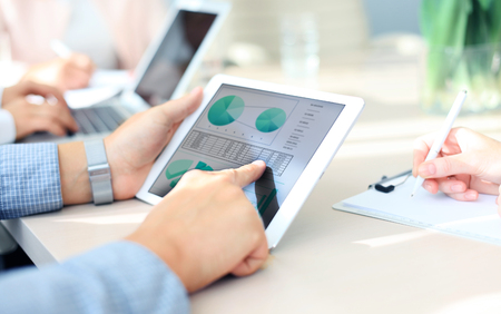 financial report: Business person analyzing financial statistics displayed on the tablet screen