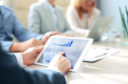 tableta: Oříznuté snímek skupiny podnikatelů při pohledu na grafy na digitálních tablet