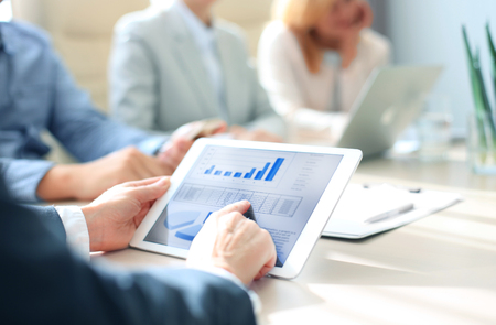 informe: Recortar foto de un grupo de empresarios mirando gráficos en tabletas digitales