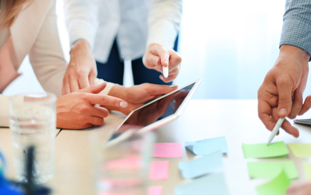 Collègues discuter de la situation financière de leur entreprise sur une tablette numérique