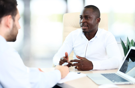 Image of two young businessmen interacting at meeting in office Imagens