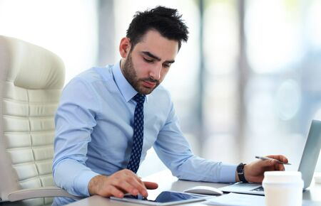 ejecutivo en oficina: Apuesto hombre de negocios que trabajan con ordenador port�til en la oficina