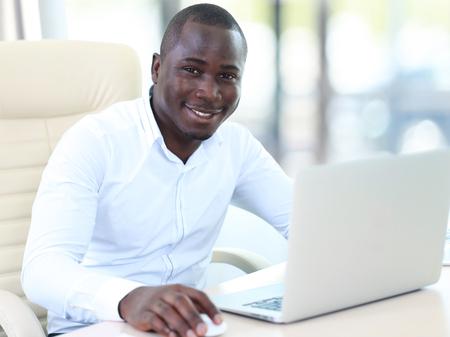 tecnología informatica: Imagen de hombre afroamericano que trabaja en su computadora portátil.
