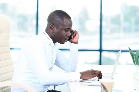 African American businessman on the phone sitting at the computer in his office Imagens