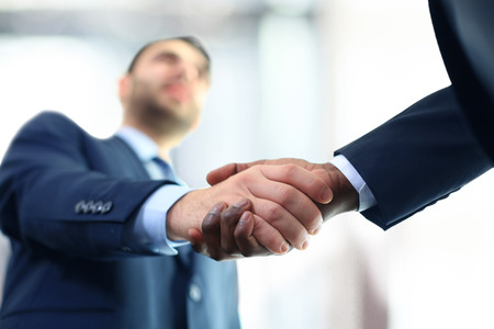 Business handshake. Business man giving a handshake to close the deal Imagens