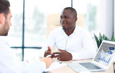 オフィスでの会議で相互作用する 2 つの若手ビジネスマンのイメージ 写真素材