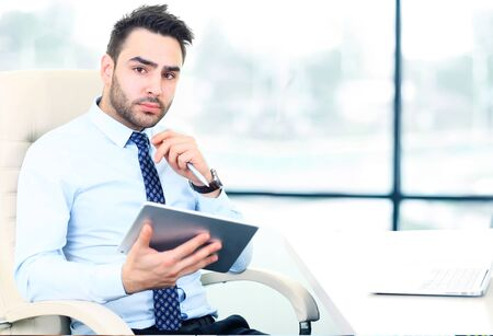 busy beard: Serious young businessman working on tablet in office
