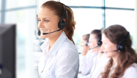 set: Smiling female customer service representative talking on headset with colleagues in background at office