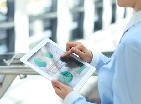 Bedrijfs persoon analyseren van financiële statistieken op het tablet-scherm