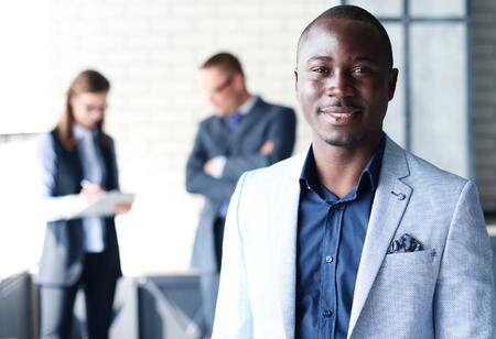 ethnicity: Happy black business man with people in the background Stock Photo
