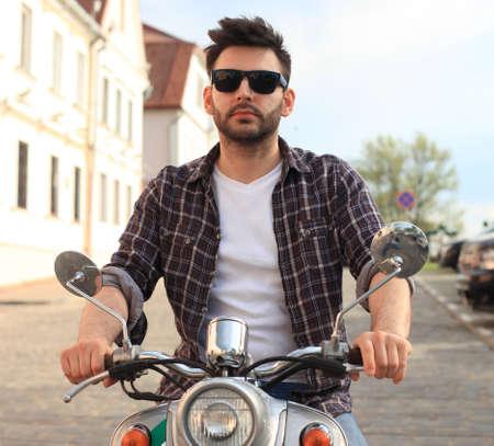 el hombre de moda joven montado en un scooter de la vendimia en la calle