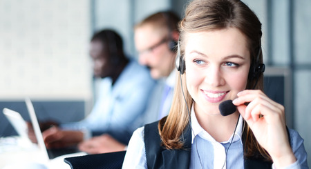 Portrait of call center worker accompanied by her team. Smiling customer support operator at work. Banco de Imagens