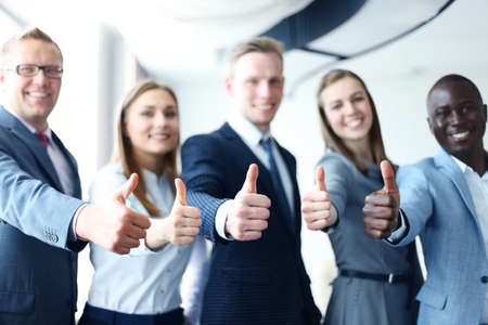 happy business team: Portrait of happy businesspeople standing in office showing thumb up
