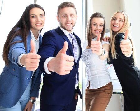 Portrait of happy Geschäftsleute stehen im Büro mit Daumen nach oben