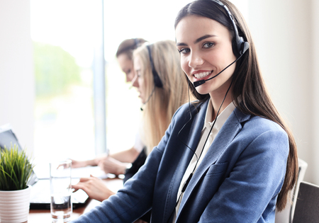 Portrait of call center worker accompanied by her team. Smiling customer support operator at work. Imagens