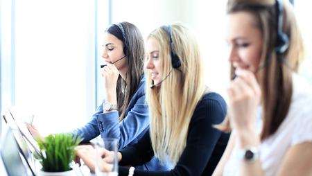 Portrait of call center worker accompanied by her team. Smiling customer support operator at work. Stok Fotoğraf