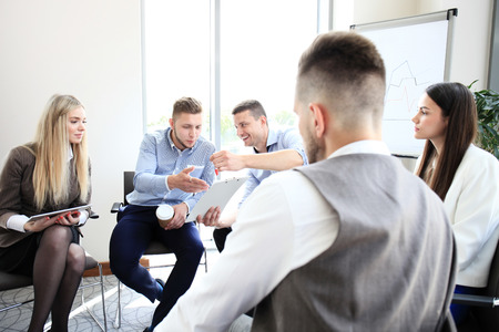 group meeting: Group of young business professionals having a meeting. Diverse group of young designers smiling during a meeting at the office. Stock Photo