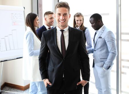 mates: Happy smart businessman with team mates discussing in the background