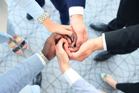 Multiethnic group of young people putting their hands on top of each other. Close up image of young business people making a stack of hands. Stock fotó
