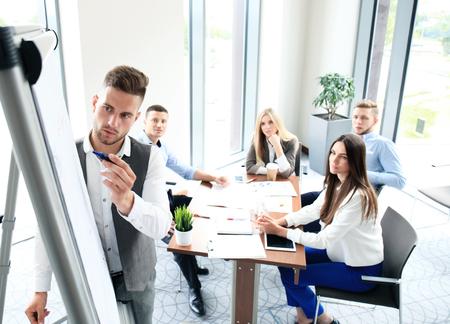 Homme d'affaires donnant une présentation sur paperboard. concept de travail d'équipe
