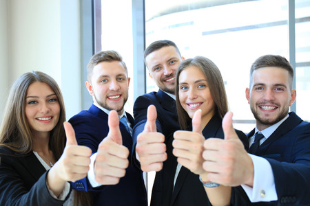 businesspeople: Portrait of happy businesspeople standing in office showing thumb up