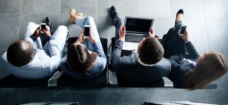 Groep van aantrekkelijke jonge bussinespeople zittend op de stoelen met behulp van een laptop, tablet-pc's, smartphones, glimlachend Stockfoto