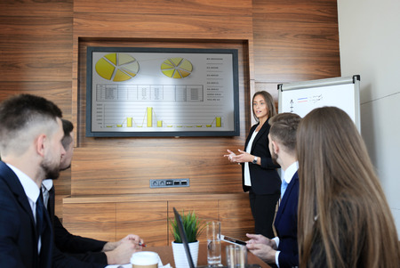 Business training at office, business woman presenting successful financial numbers on screen of plasma TV at meeting room